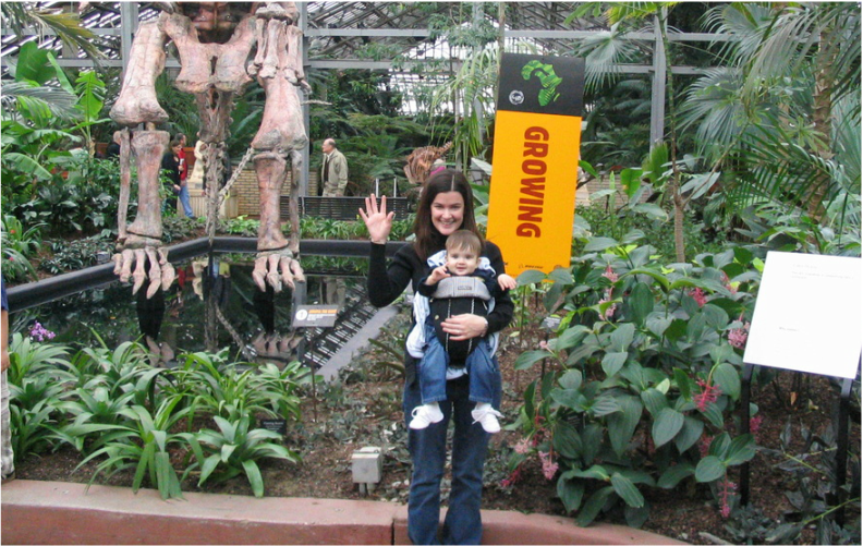2004 at Navy Pier while traveling in Chicago. I'm a white woman with dark hair and dark clothing wearing my white son at 11 months, forward-facing in a Baby Bjorn. I am waving at the camera, he is smiling, and there are leafy plants and dinosaur bones in a touristy background.