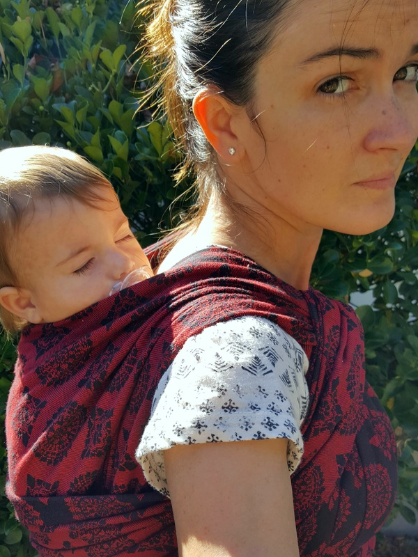 Review of Soul Imperial, Rainbow's Back Carry [Image of me, a thin white woman with dark hair, wearing my sleeping white baby boy in a red and black woven wrap Soul Imperial tied in Rainbow's Back Carry.]