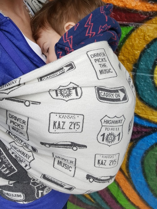 Review of the Carry On, Baby woven wrap by DBG Baby [Image showing the side of a Robin's Hip Carry in a black and white woven wrap covered in street signs with phrases from the show Supernatural, worn by a white woman and her white toddler son.]