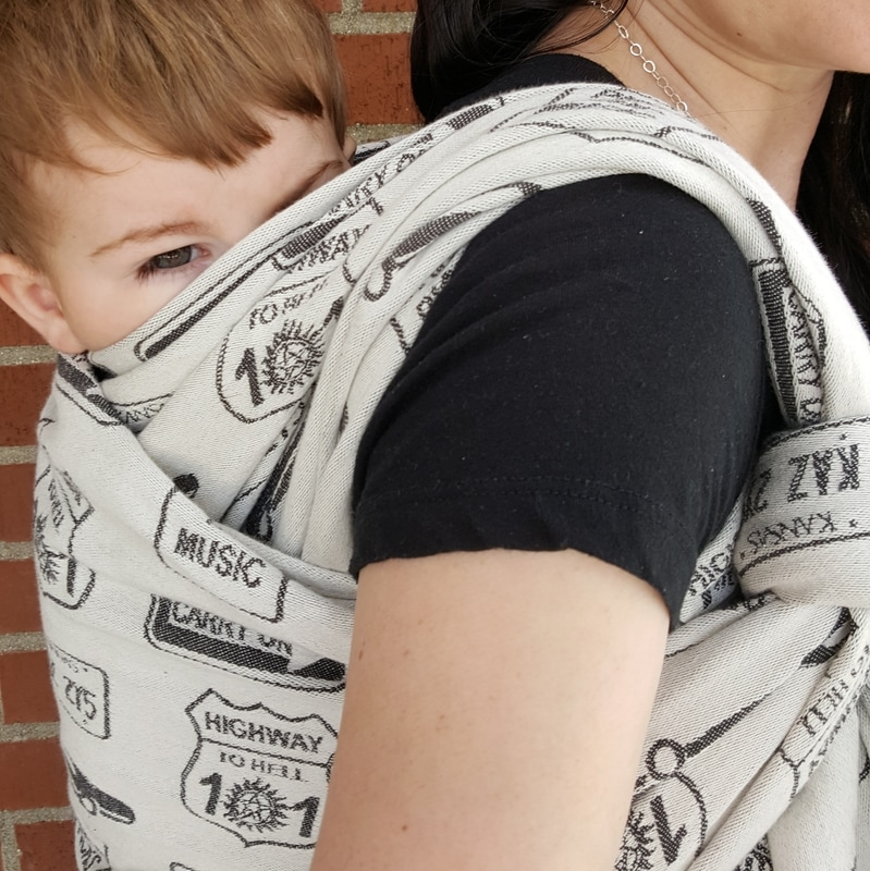 Review of the Carry On, Baby woven wrap by DBG Baby [Image taken from over shoulder showing the side of a Double Hammock back carry in a black and white woven wrap covered in street signs with phrases from the show Supernatural, worn by a white woman with dark hair and her white toddler son.]