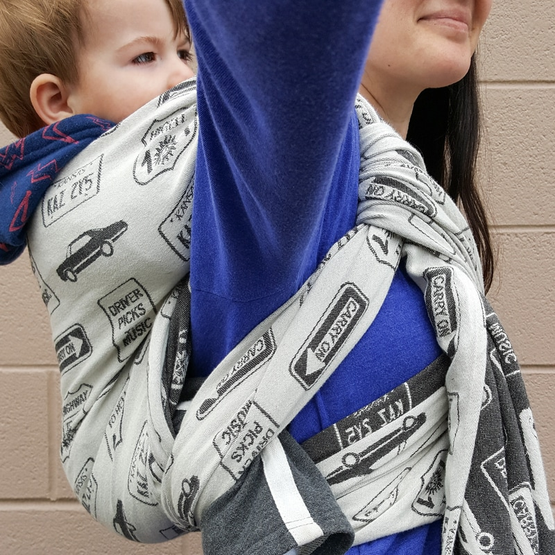 Review of the Carry On, Baby woven wrap by DBG Baby [Image taken from under arm showing the side of a Ruck back carry with a Tibetan finish in a black and white woven wrap covered in street signs with phrases from the show Supernatural, worn by a white woman with dark hair and her white toddler son.]