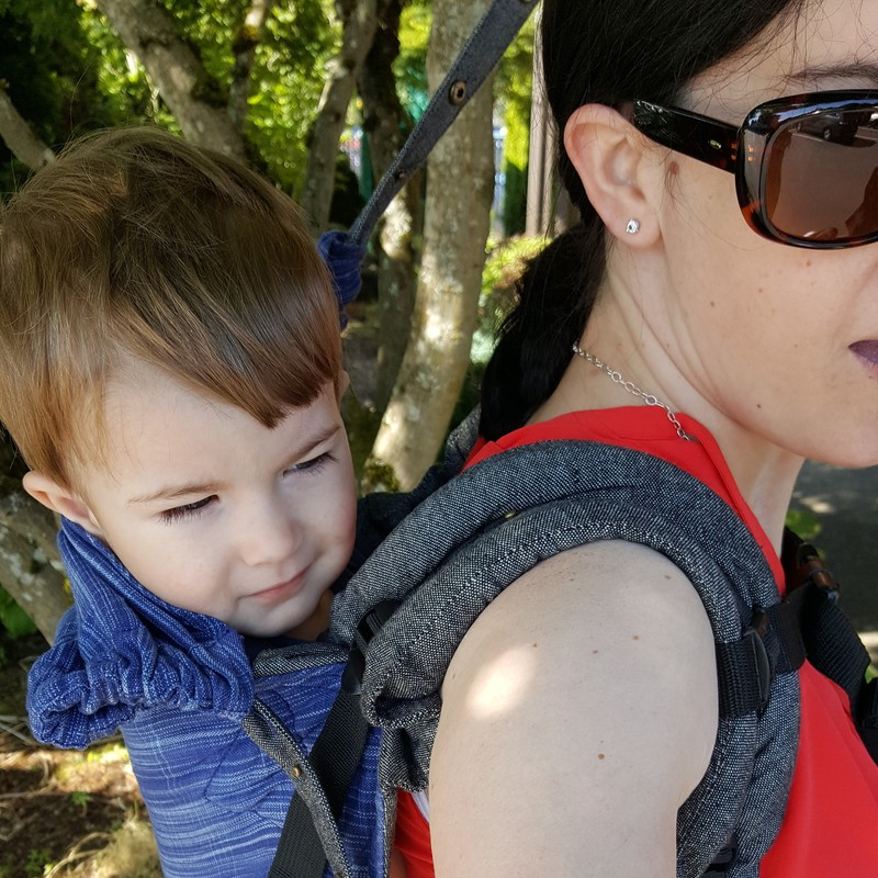 Review of the Kol Kol Onbuhimo, waistless buckle carrier [Image taken from over shoulder of a white woman wearing a white toddler on her back in a blue wrap conversion onbuhimo carrier. She's pulling the carrier's hood up on the baby's head.]