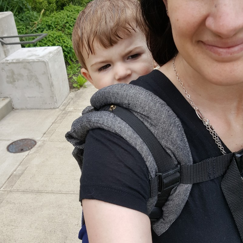 Review: Kol Kol Onbuhimo [Image taken from over shoulder of a white woman wearing a white toddler on her back in an onbuhimo carrier.  The image focuses on the padding of the shoulder strap and the baby's face peaking over shoulder.]