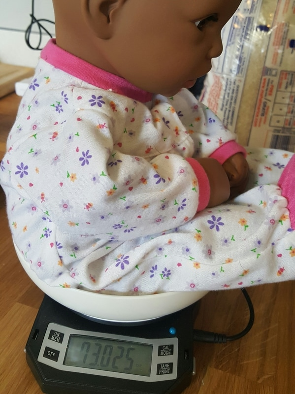 Transforming a toy store doll into a weighted demo doll [Image of a baby doll sitting on a scale. The scale reads 73 ounces or 4.5 pounds.]