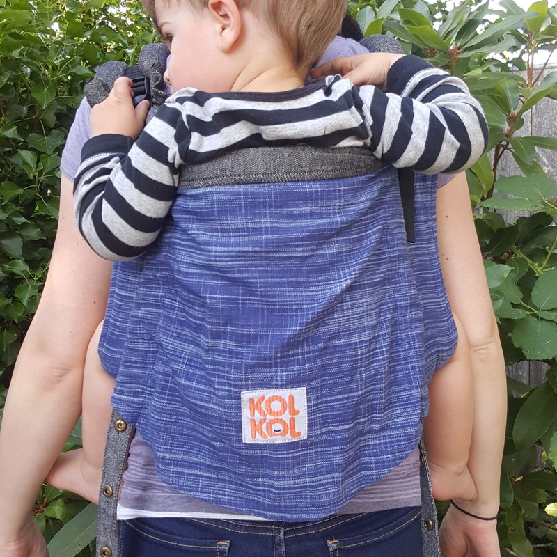 Kol Kol Onbuhimo review [Image of the back of a blue wrap conversion onbuhimo carrier worn by a white woman and her white toddler. They're in front of a leafy green background.]