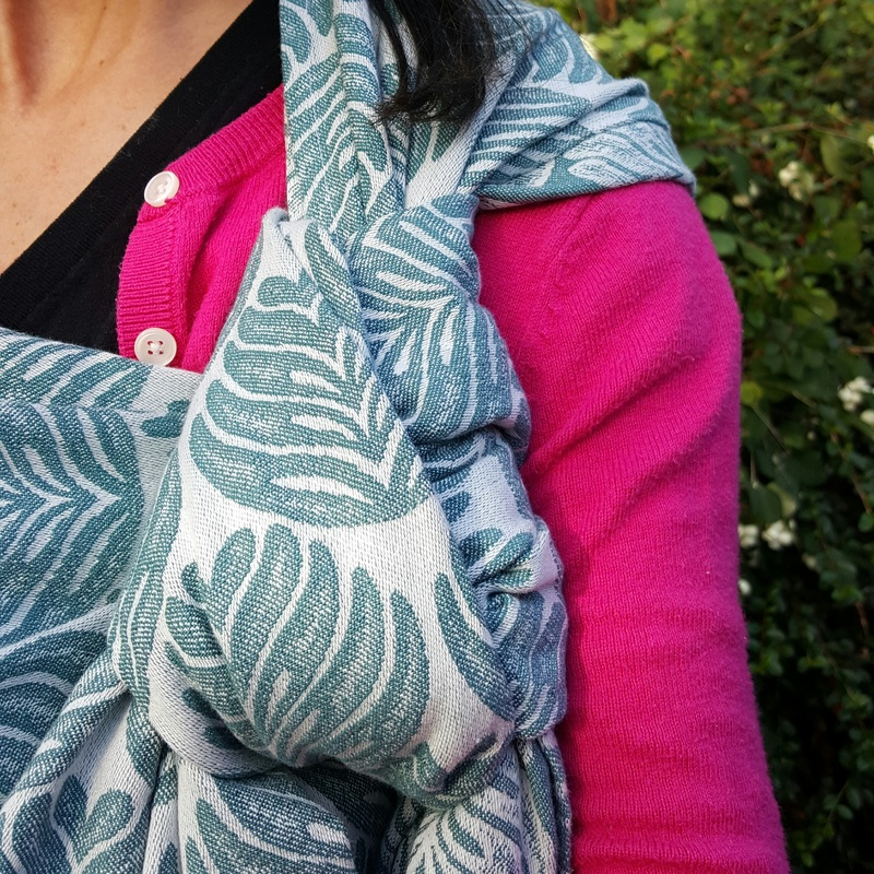 [Image: a teal blue and off white abstract leaf pattern wrap being worn by a white woman with dark hair, using it to carry her baby on her chest. She is standing in front of green plants and wearing a bright pink sweater.]