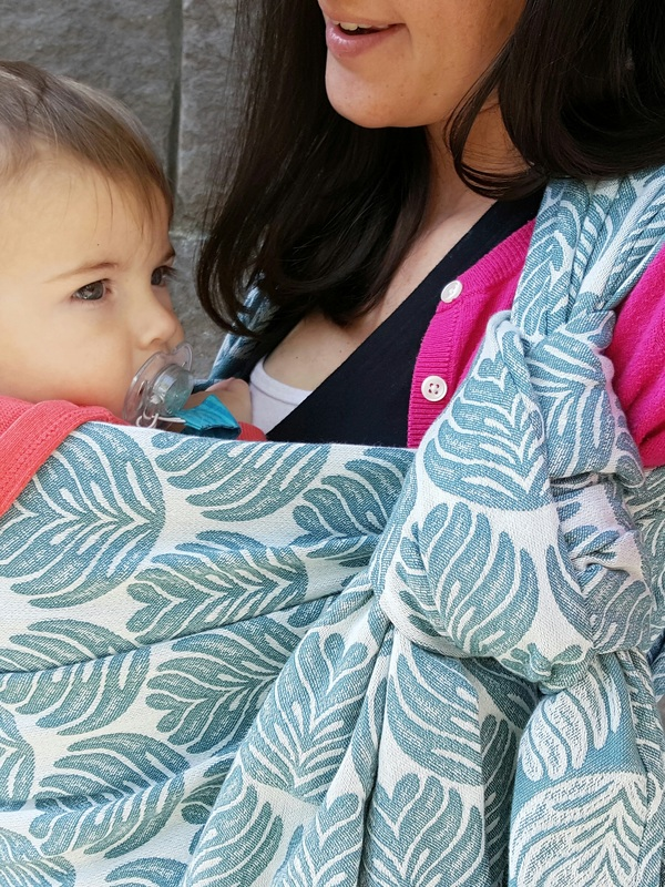 [Image: a teal blue and off white abstract leaf pattern wrap being worn by a white woman with dark hair, using it to carry her baby on her chest. She is standing in front of a grey brick wall and wearing a bright pink sweater.]